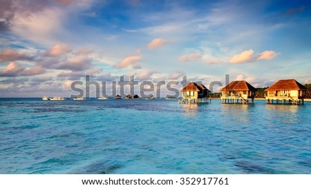 Maldivian water bungalows with blue sky and sea. - stock photo