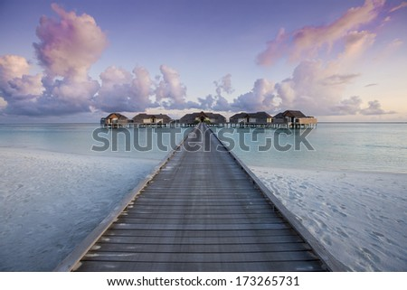 Maldivian water villas at sunset - stock photo