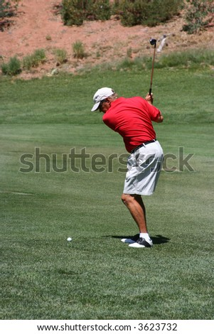 Male about to hit ball from the fairway (towards camera), focus on golfer - stock photo
