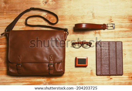 Male accessories style concent. Brown leather bag, box with french cuffs, trendy wooden rim glasses, leather belt and gadget in brown leather crocodile-textured case over wooden background. Copy space - stock photo