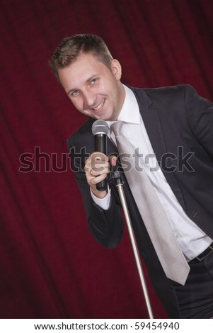 male actor with microphone on the stage - stock photo