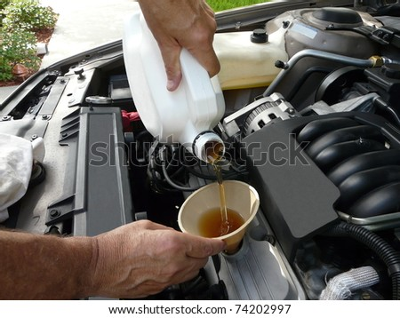 Male adding oil with a funnel after a do-it-yourself oil change. - stock photo
