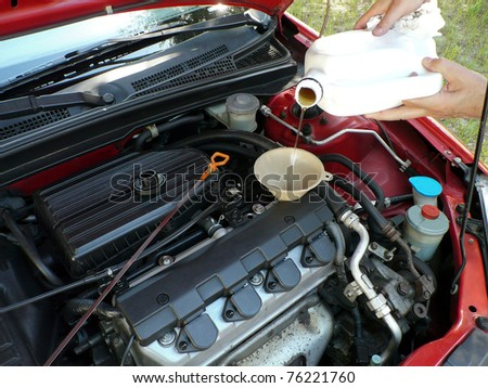 Male adding oil with a funnel after an oil change. Dipstick is nearby. - stock photo