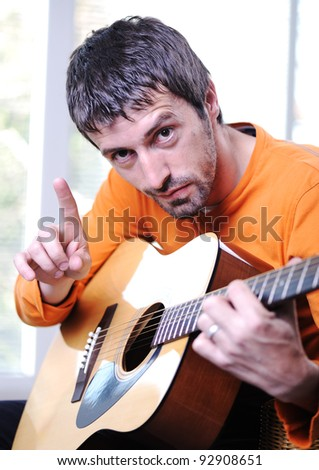 Male adult playing guitar - stock photo