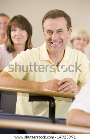 Male adult student listening to a university lecture - stock photo