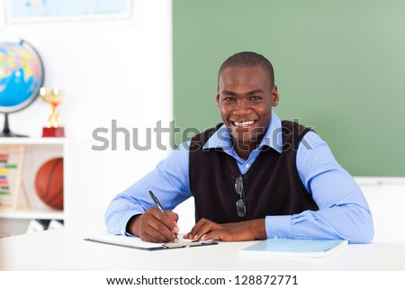 male african american school teacher preparing class in classroom - stock photo