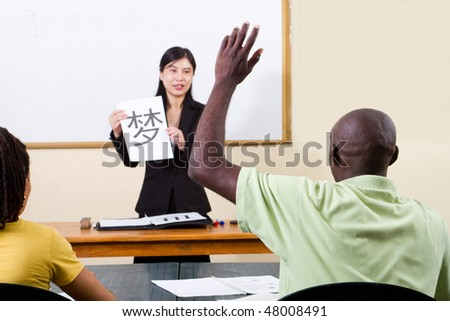 male african american student raising hand in chinese classroom - stock photo