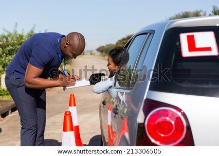 male african driving instructor and student driver in testing ground - stock photo