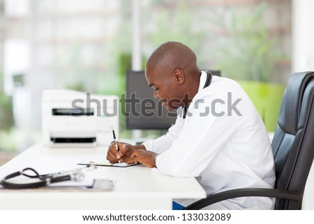 male african medical doctor writing reports in his office - stock photo