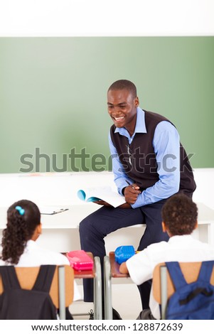 male african primary school teacher teaching in classroom - stock photo