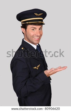 Male airline pilot smiling holding hand out