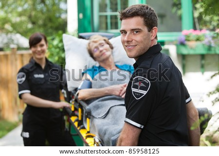 Male ambulance professional with happy senior woman on stretcher - stock photo