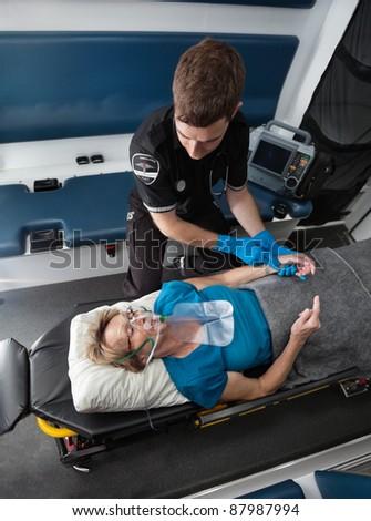 Male ambulance worker taking pulse of elderly senior woman - stock photo