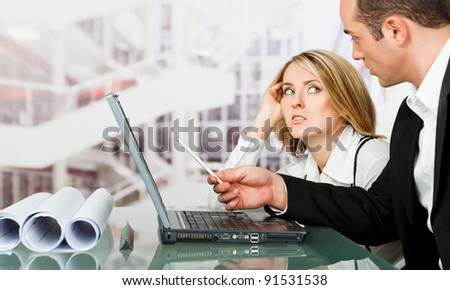 Male and female architects discussing work behind laptop, looking serious