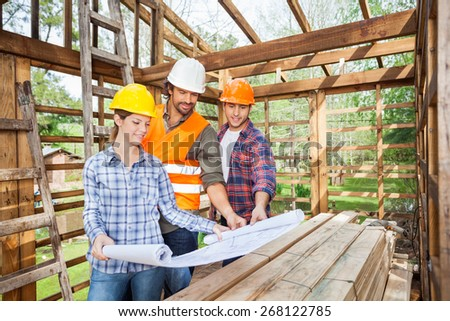 Male and female architects studying blueprint in wooden cabin at site - stock photo