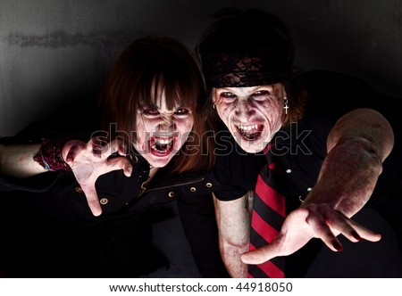 Male and female bloody zombies reaching out