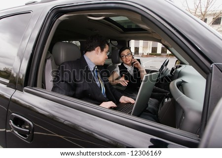 Male and female business colleagues working on a laptop while sitting in a car - stock photo