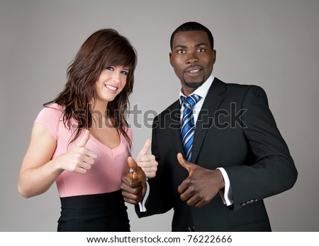 Male and female business partners going thumbs up. - stock photo