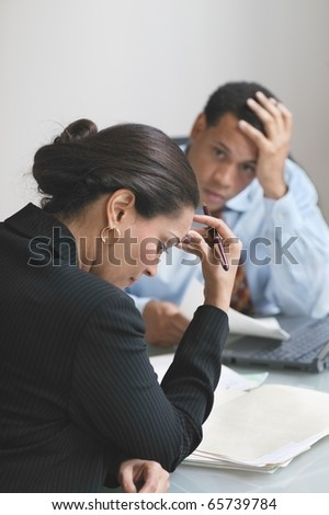 Male and female business partners reviewing paperwork