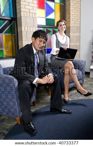 Male and female business people sitting on armchairs in office reception area - stock photo