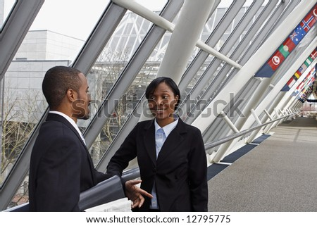 Male and female businesspeople having an impromptu meeting in an office lobby