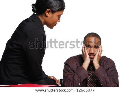 Male and female businesspeople interacting. She is sitting on the desk talking to him and he has his face in his hands looking fed up. Isolated against a white background