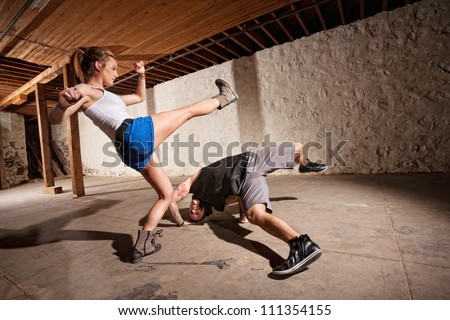 Male and female capoeria sparring partners working out - stock photo