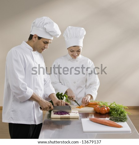 Male and female chef chopping vegetables - stock photo