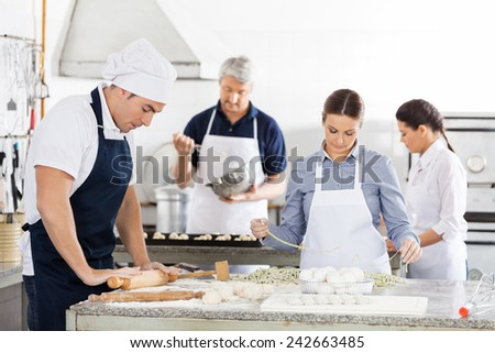 Male and female chefs making pasta together in commercial kitchen - stock photo