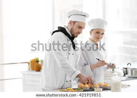 Male and female chefs working at kitchen - stock photo