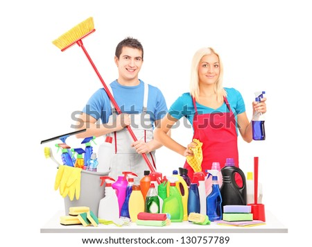 Male and female cleaners posing with cleaning supplies on a table isolated on white background - stock photo