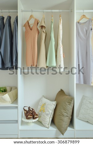 Male and female clothes hanging on hangers in wardrobe - stock photo