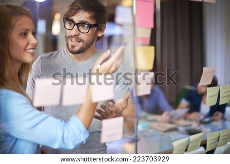 Male and female colleagues discussing notes on paper reminders in office