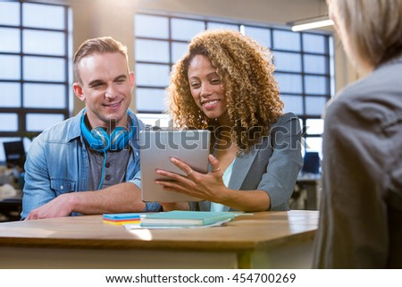 Male and female colleagues smiling while looking in tablet computer in creative office