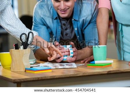 Male and female colleagues working at desk in creative office - stock photo