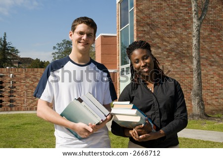 male and female college students carrying textbooks