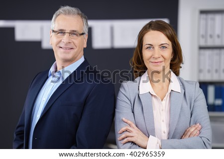 Male and female confident middle aged business people grinning while standing in front of wall of charts and bookshelf in office