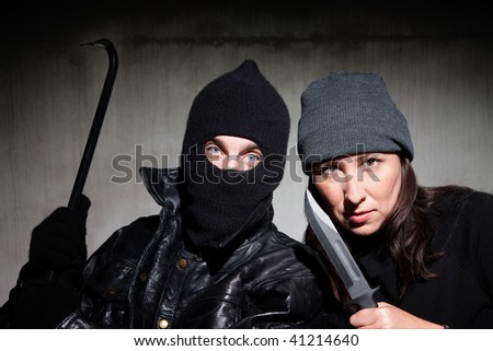 Male and female criminals wielding dangerous weapons - stock photo