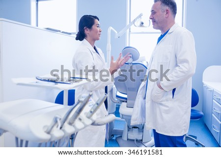 Male and female dentists discussing at dental clinic - stock photo