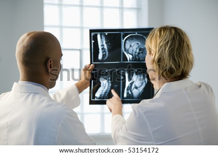 Male and female doctor looking at patient xray film. - stock photo
