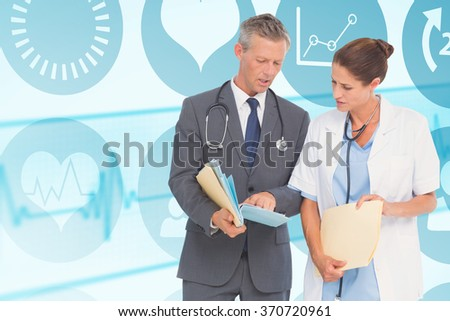 Male and female doctors discussing over reports against medical background with blue ecg line - stock photo