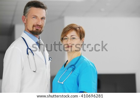 Male and female doctors in the hospital, indoors - stock photo