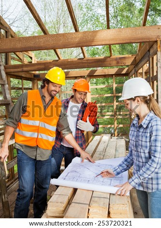 Male and female engineers working on blueprint in incomplete wooden cabin at site - stock photo