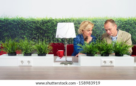 Male and female environmentalists working at desk in office - stock photo