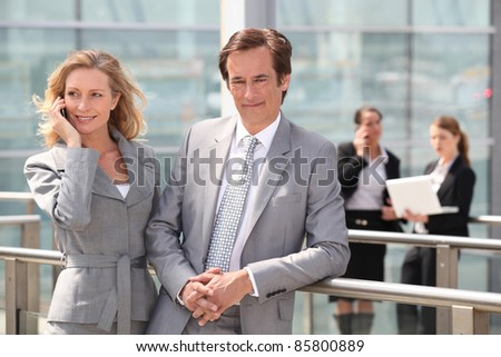 Male and female executives outside conference center - stock photo