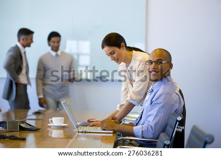 Male and female executives working together in a meeting room with trainer using white board in the background. - stock photo