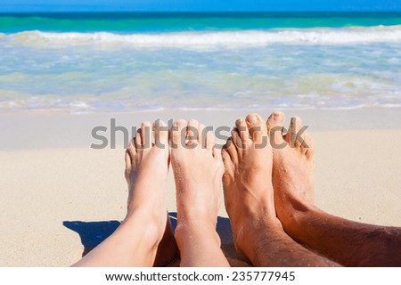 Male and female feet at the beach. Vacation concept. - stock photo