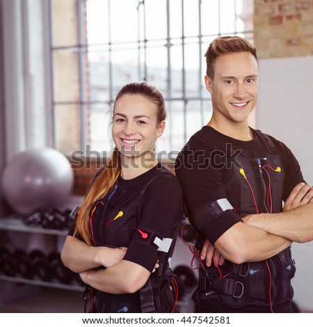 Male and female fitness instructors stand together while wearing ems outfits in exercise studio near tall windows - stock photo
