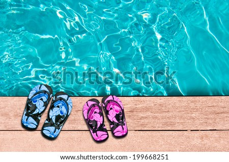 Male and female flip flops and swimming poll close-up - stock photo