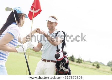 Male and female friends giving high-five at golf course - stock photo